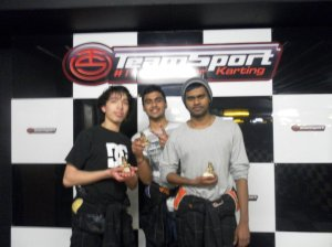 Alex, Kiran and Praveen celebrate the team's victory on the podium.
